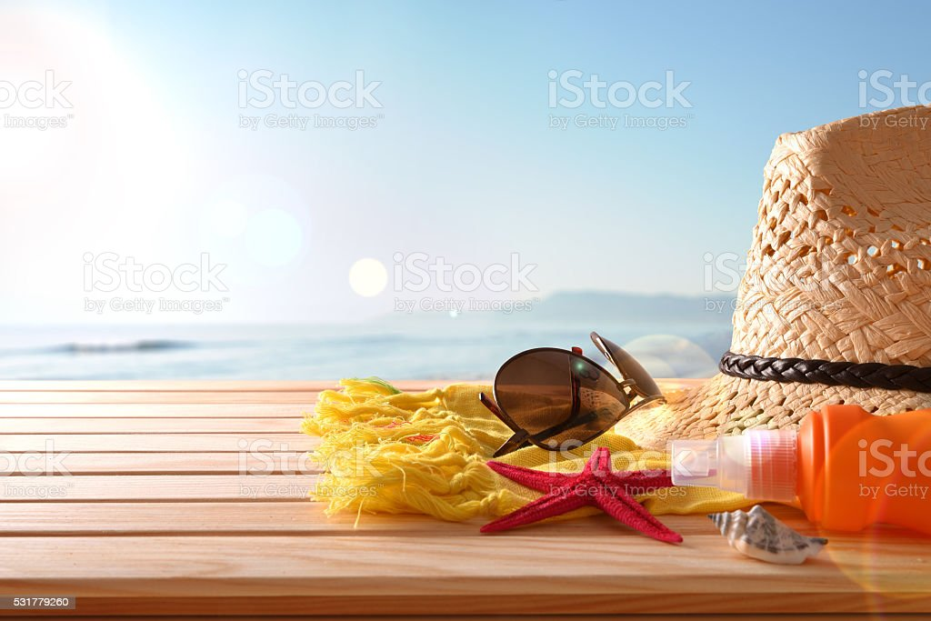 Beach articles on a table wooden slats and sea background stock photo