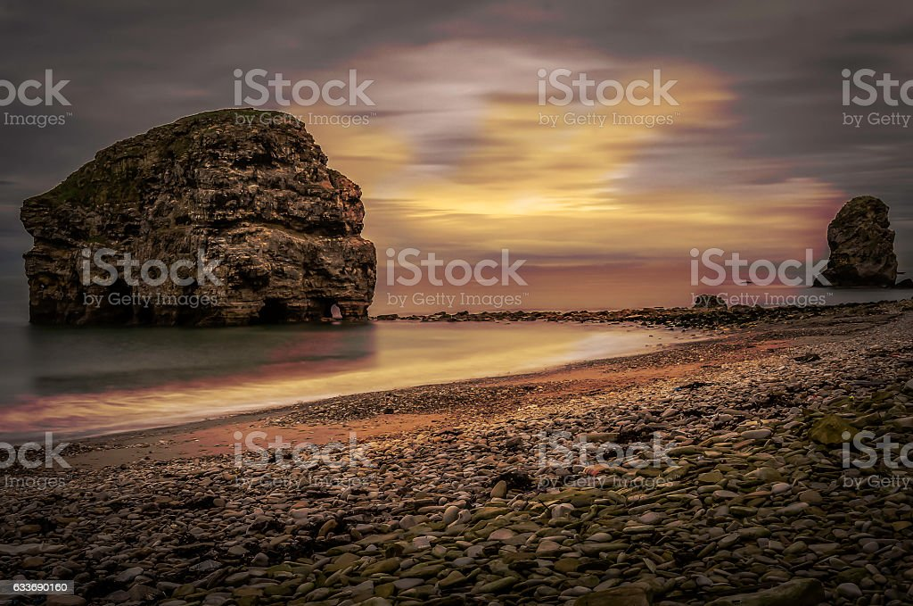 beach at sunset pebble beach with large rock structure stock photo
