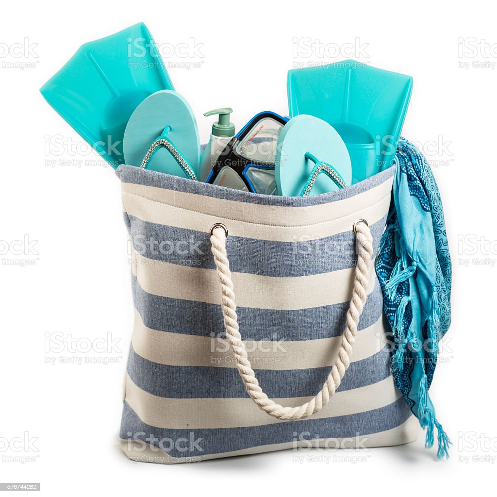 Beach bag with items isolated on white background stock photo