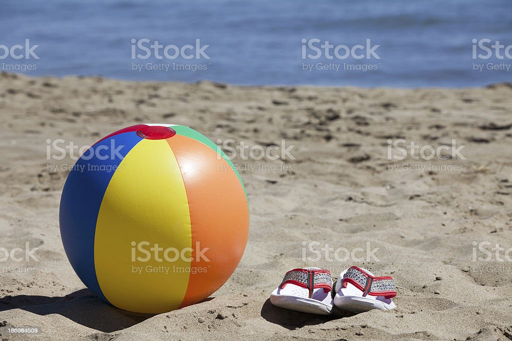 Beach Ball and Flip-Flops in the Sand stock photo