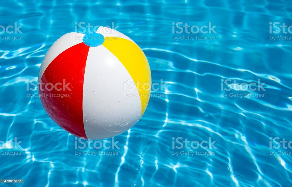 A beach ball floating in a blue pool stock photo