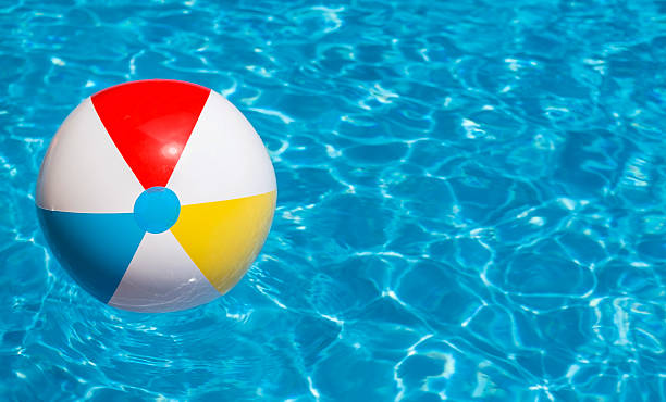 Colorful beach ball floating in a swimming pool pictures - How to make swimming pool water blue ...
