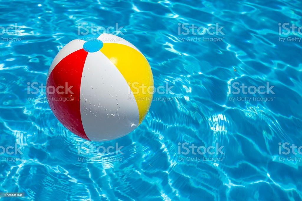 Beach Ball In Water beach ball party in a blue water swimming pool stock photo