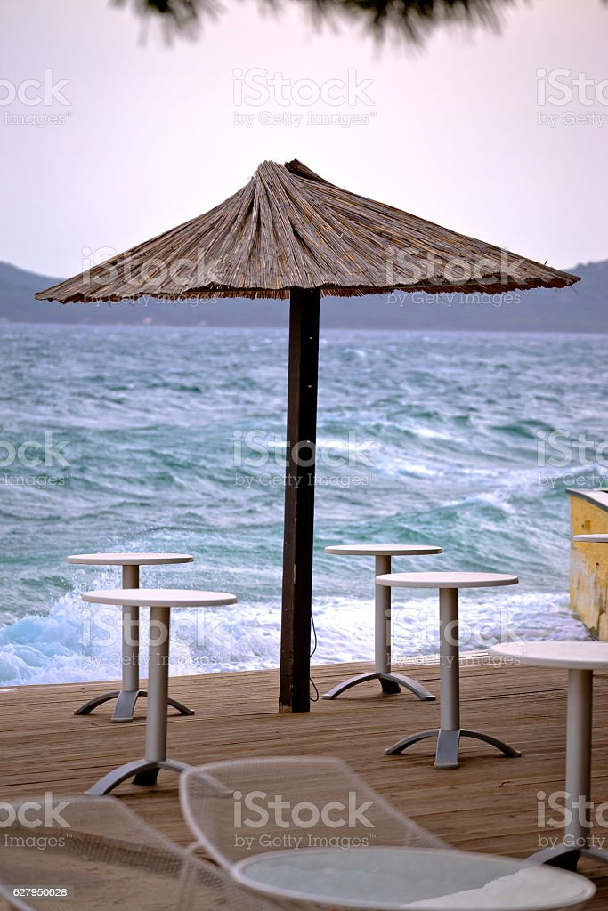 Beach bar parasol by rough sea stock photo