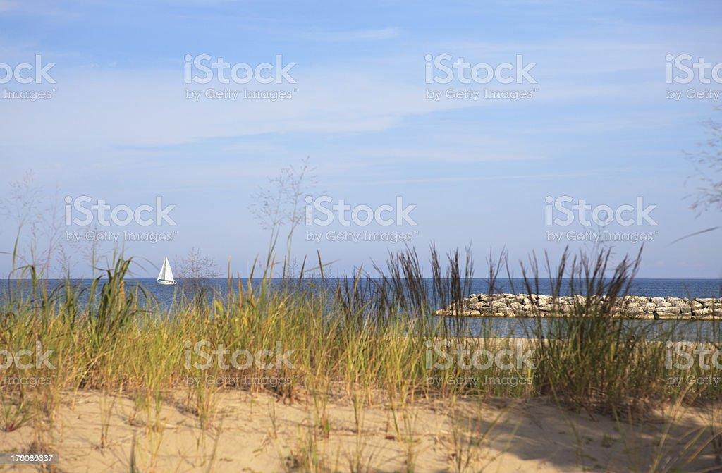 Beach breakwater and sailboat stock photo