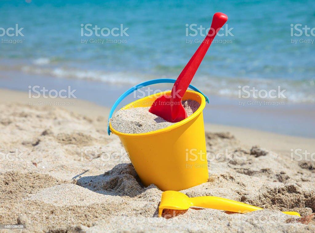 Beach bucket full of sand sitting on beach stock photo