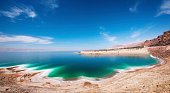 A beach by the Dead Sea with blue skies and turquoise water