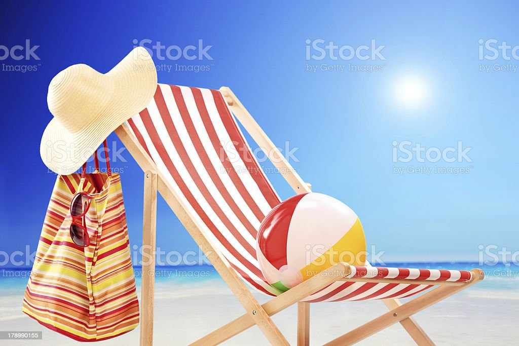 Beach chair with ball, bag and hat by the sea royalty-free stock photo