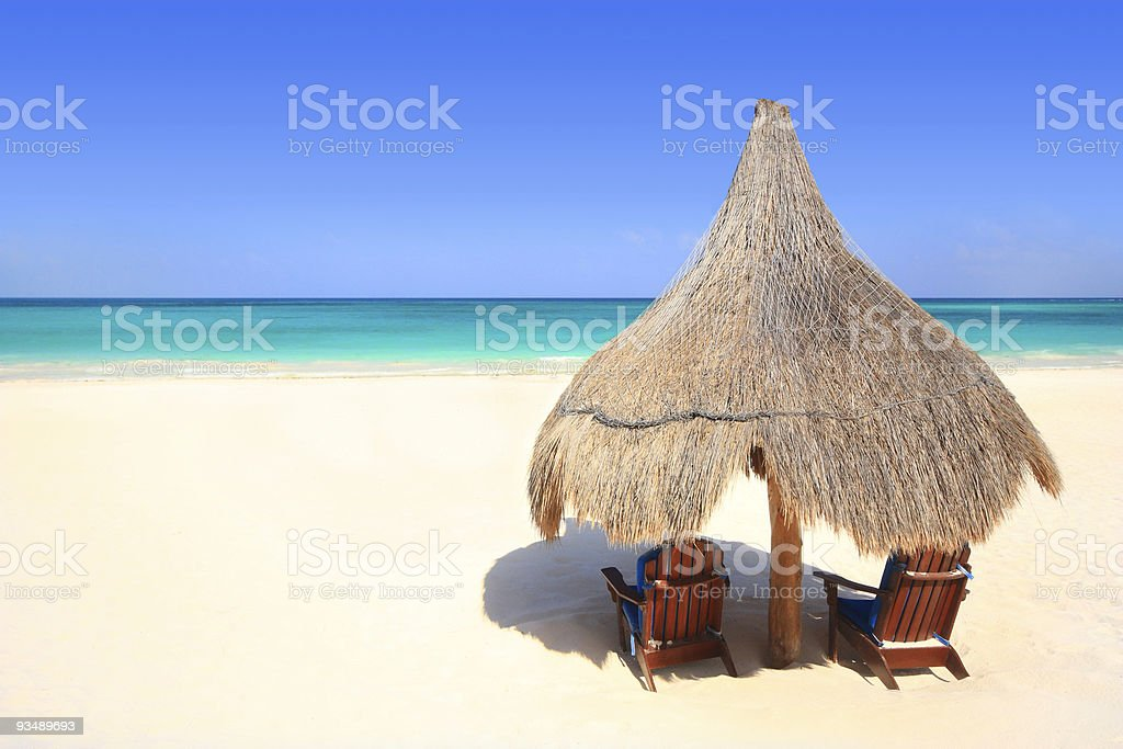 Beach chairs and palapa thatched umbrella overlooking the ocean stock photo