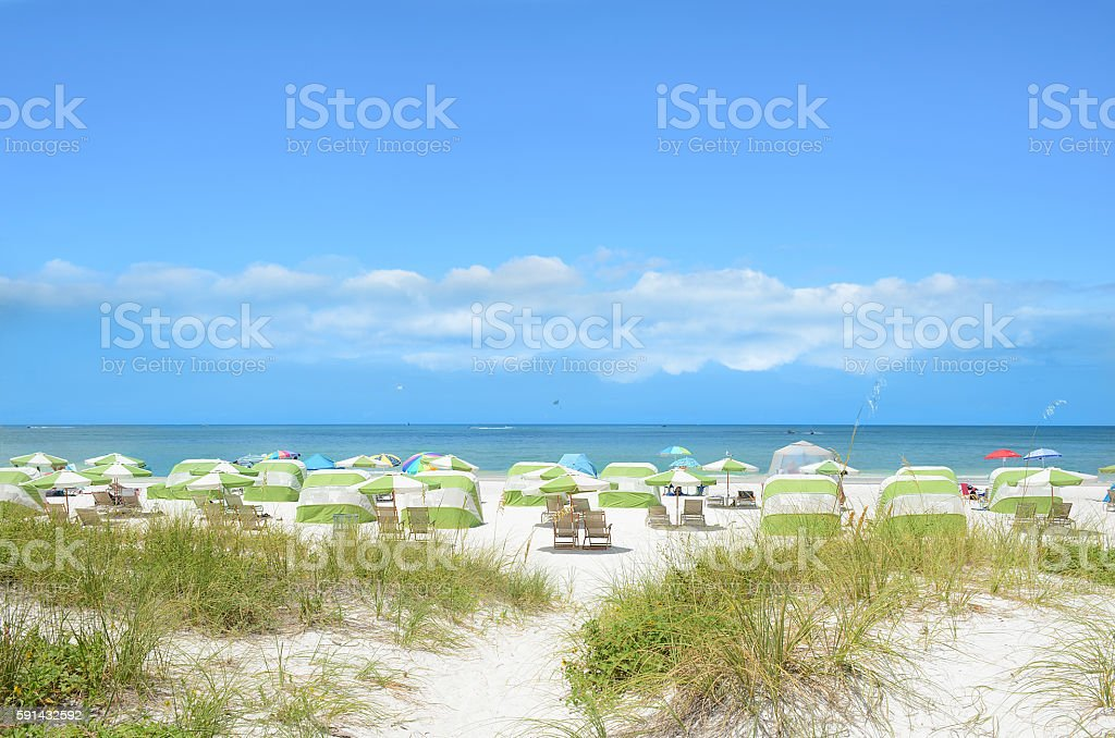 Beach chairs and parasols on beautiful white beach. stock photo