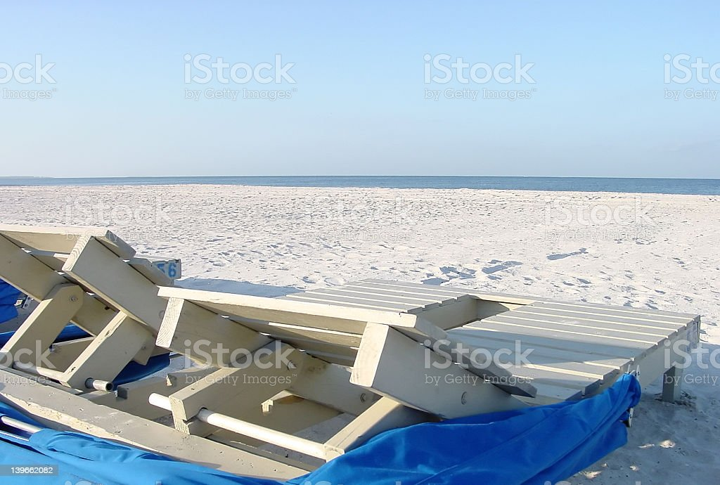 Beach chairs looking out on sand and water royalty-free stock photo