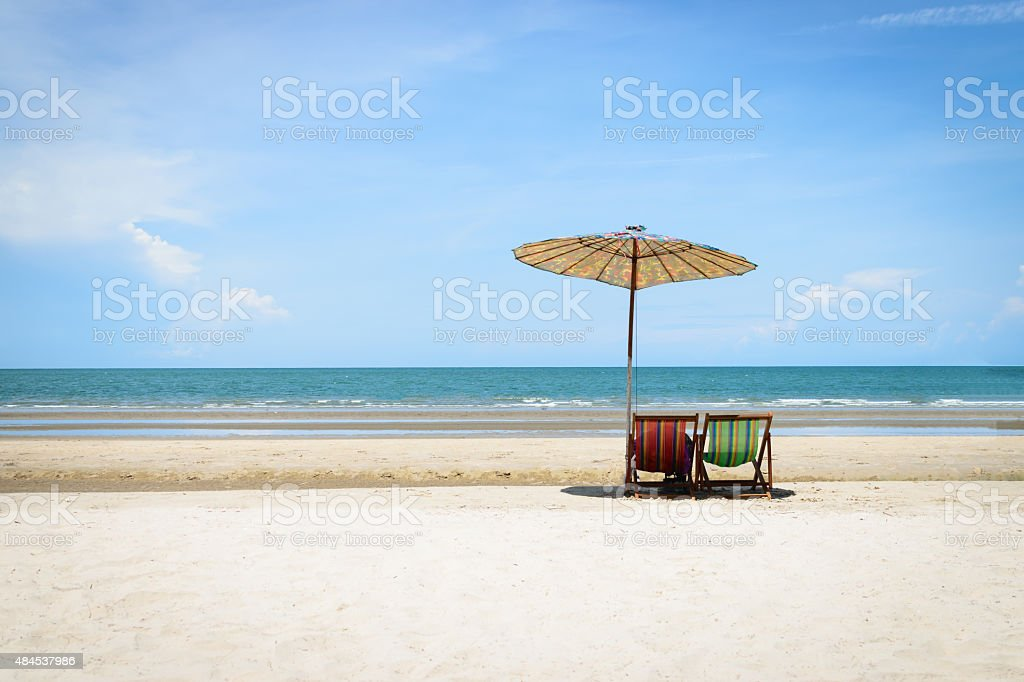 Beach chairs on the sand beach with cloudy blue sky background stock photo