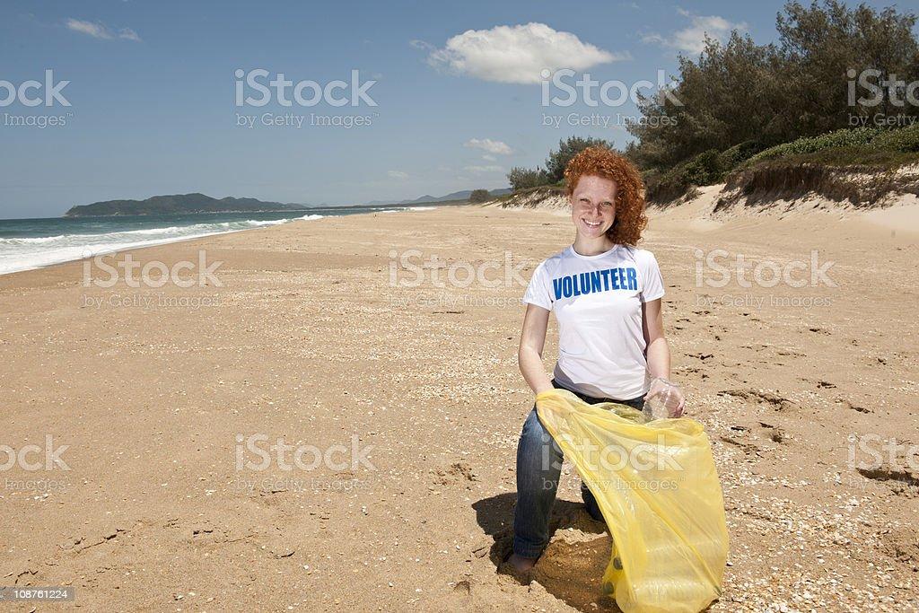 Beach clean up: happy volunteer stock photo