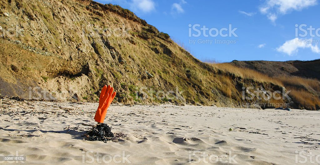 Beach clean up - rubber glove pointing towards the sky stock photo