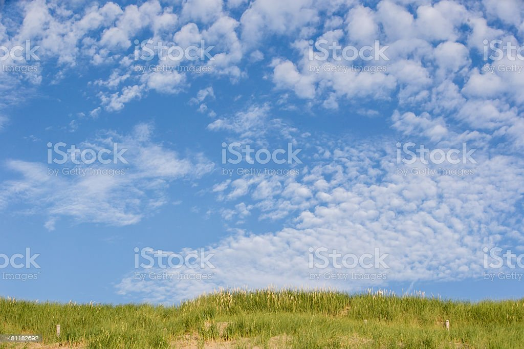 Beach coast with dunes on a sunny day with clouds stock photo
