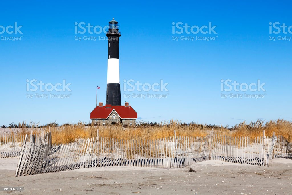 Beach Fence and Lighthouse stock photo