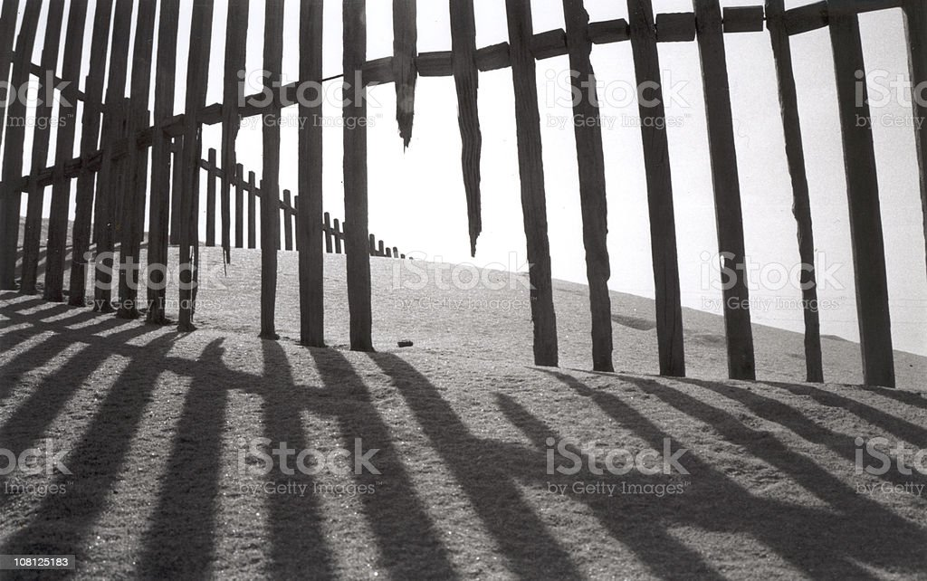 Beach Fence in Sand, black and white royalty-free stock photo