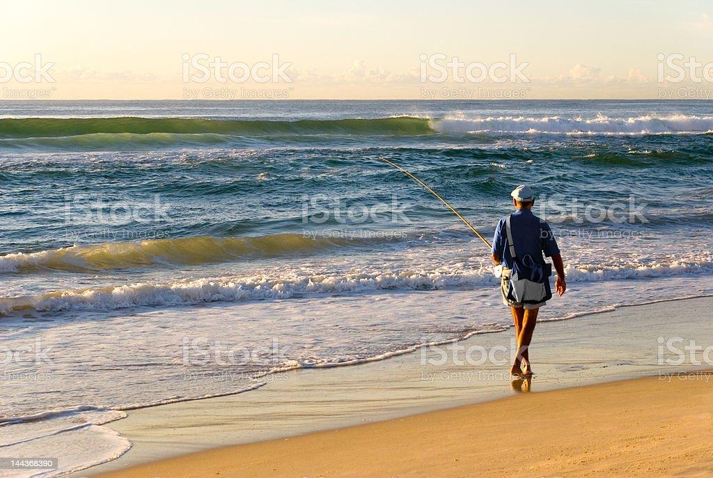 Beach Fisherman by Ocean as Sun rises royalty-free stock photo
