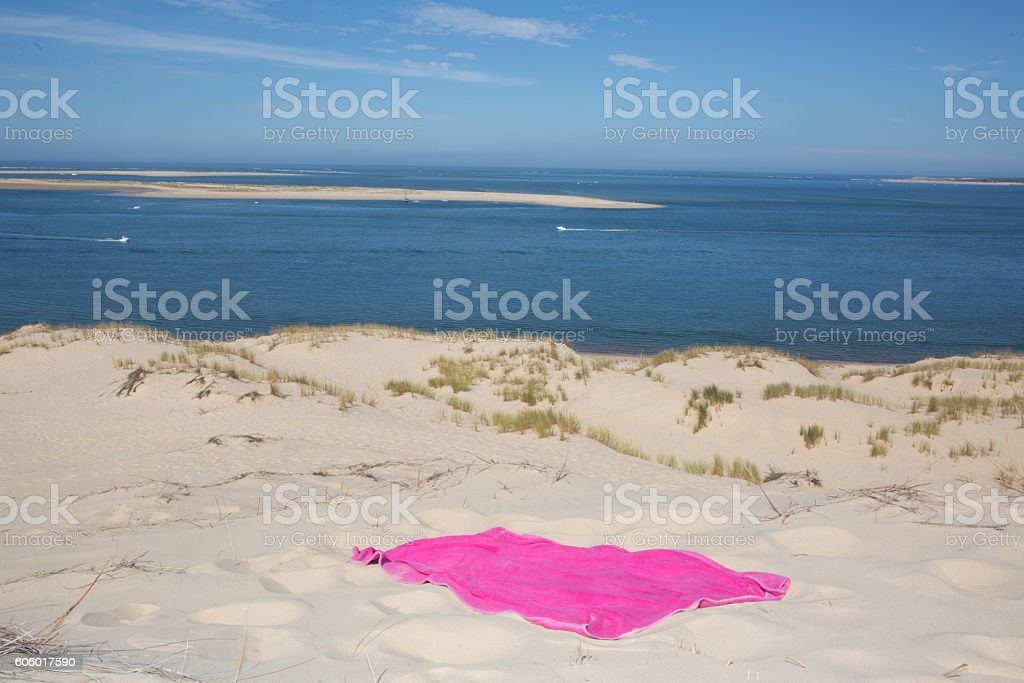 Beach holiday and travel concept with a pink beach towel stock photo