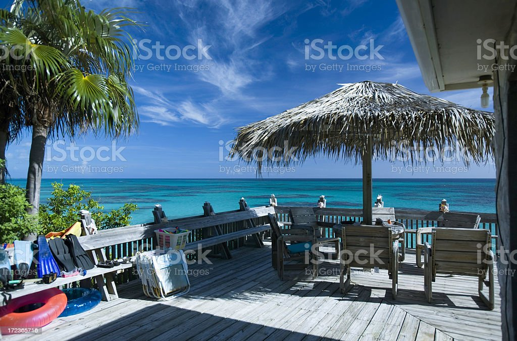 Beach house deck with umbrella and chairs royalty-free stock photo