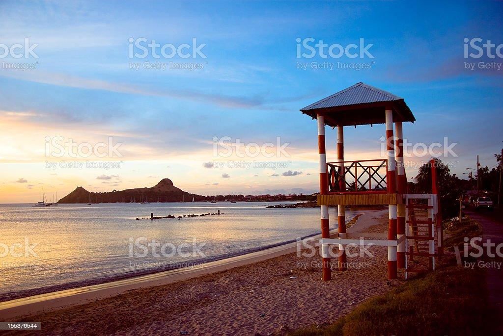 beach hut and distant cape island stock photo