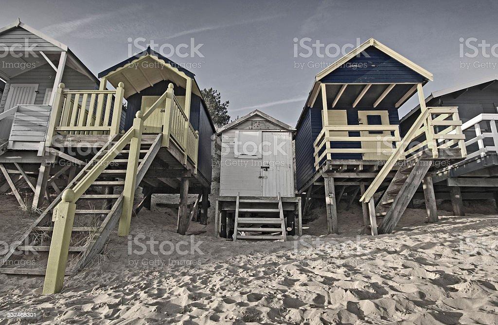 Beach huts, moody, dramatic, sand and sea stock photo