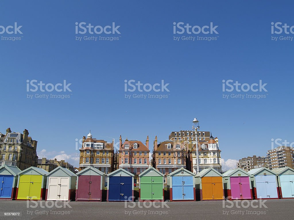 Beach Huts of Brighton/Hove with traditional buildings background. stock photo