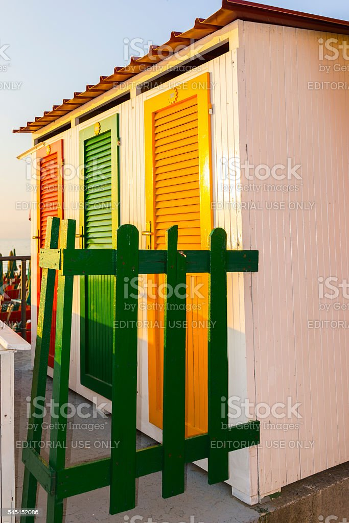 Beach huts with colored doors and a green fence stock photo