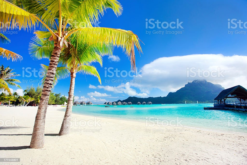 A beach in BoraBora with a blue sea, white sand and sun  stock photo