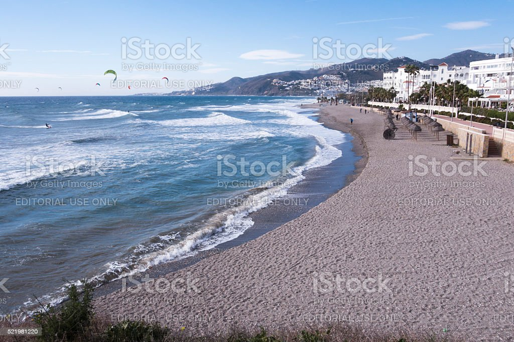 Beach in Nerja on a windy day with windsurfers stock photo