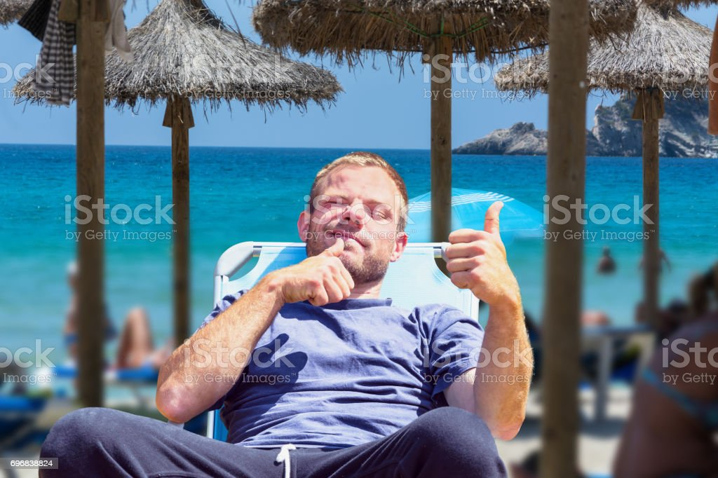 Beach life picture with desired blur. Focus on man in deck chair. stock photo