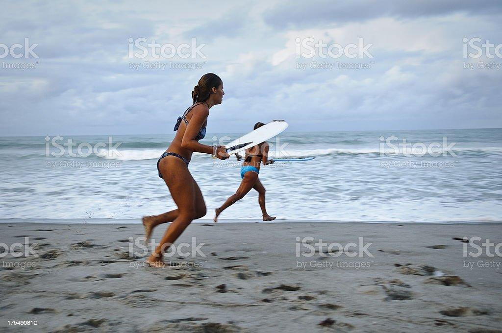 Beach lifestyle: skimboarding young women stock photo