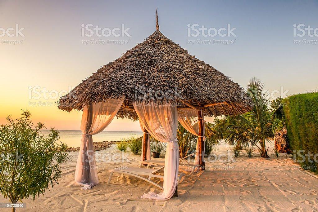 Beach lounge chairs at sunset, Zanzibar, Tanzania stock photo