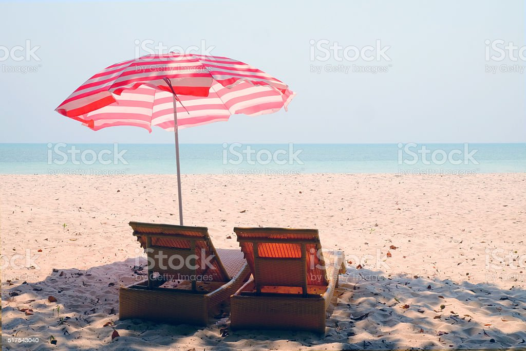 Beach loungers on a sandy beach. stock photo