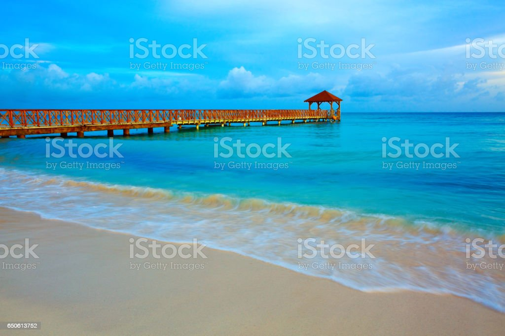 Beach of caribbean sea and wooden pier stock photo