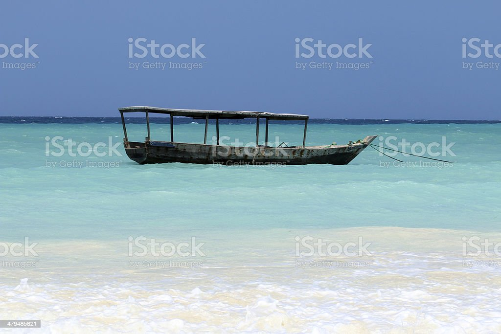 Beach of Zanzibar with traditional fisherman wooden dhow boat, Tanzania. stock photo