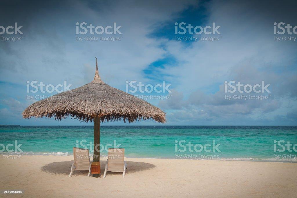 Beach parasol and sun lounger stock photo