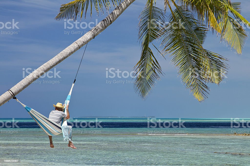 Beach relaxation in hammock hanged in paradise stock photo