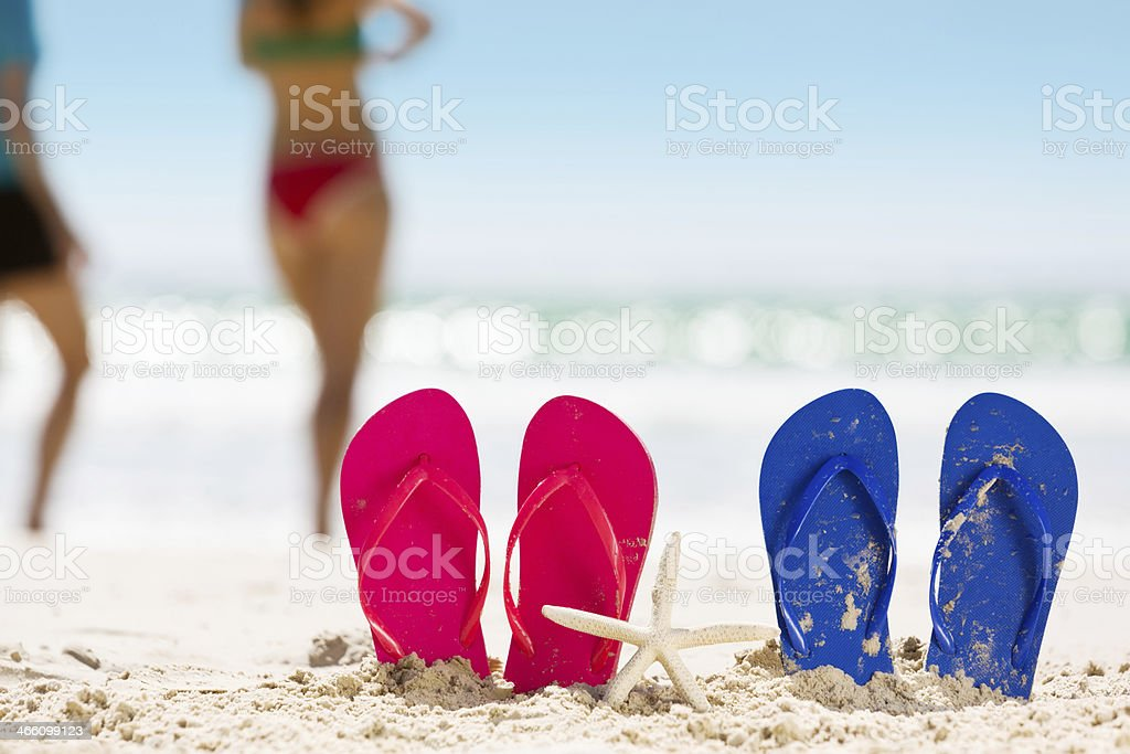Beach relaxation time, with flipflops in the sand stock photo