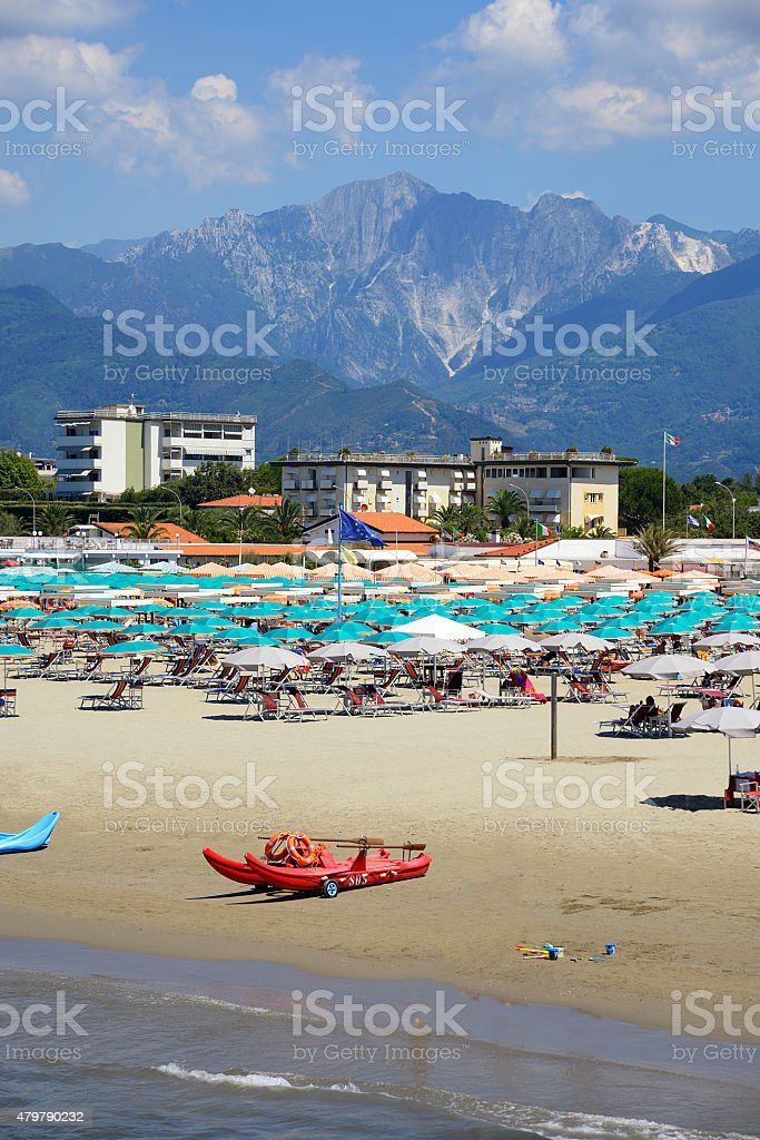 Beach resort in tuscany italy with marble mountains in background stock photo