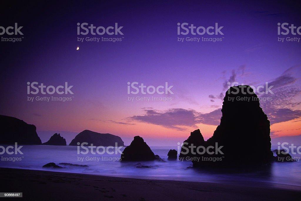 beach rock formations moonrise sunset stock photo