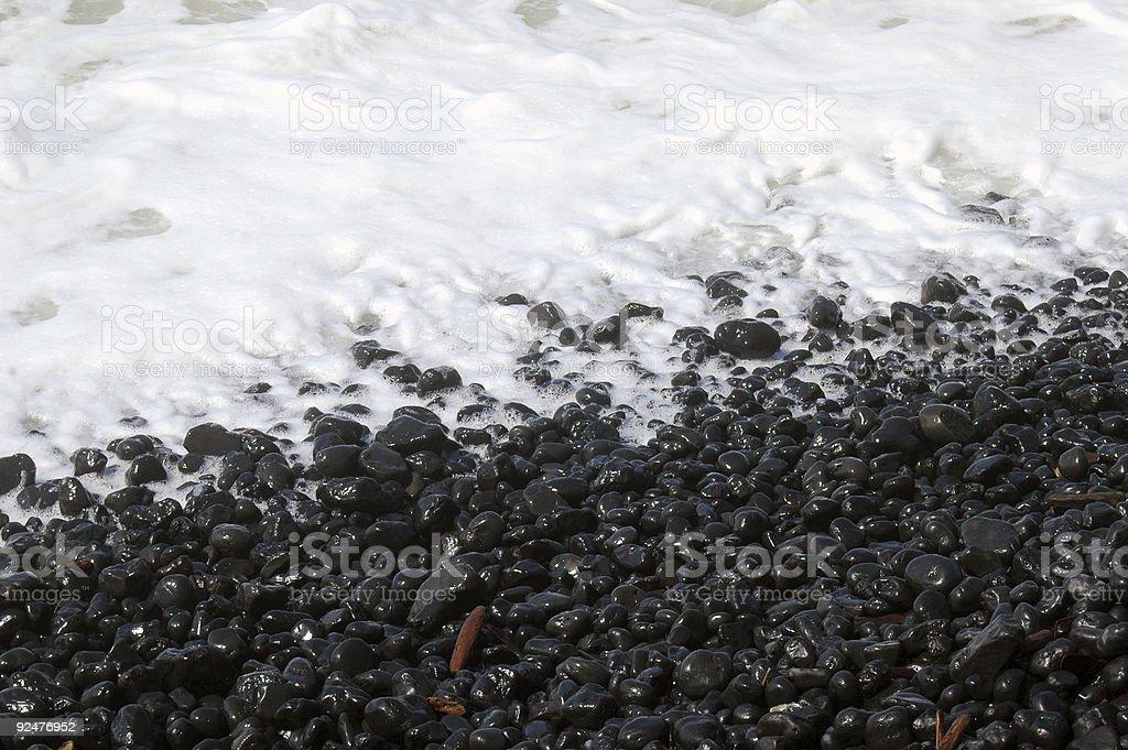 Beach rocks in sea foam royalty-free stock photo