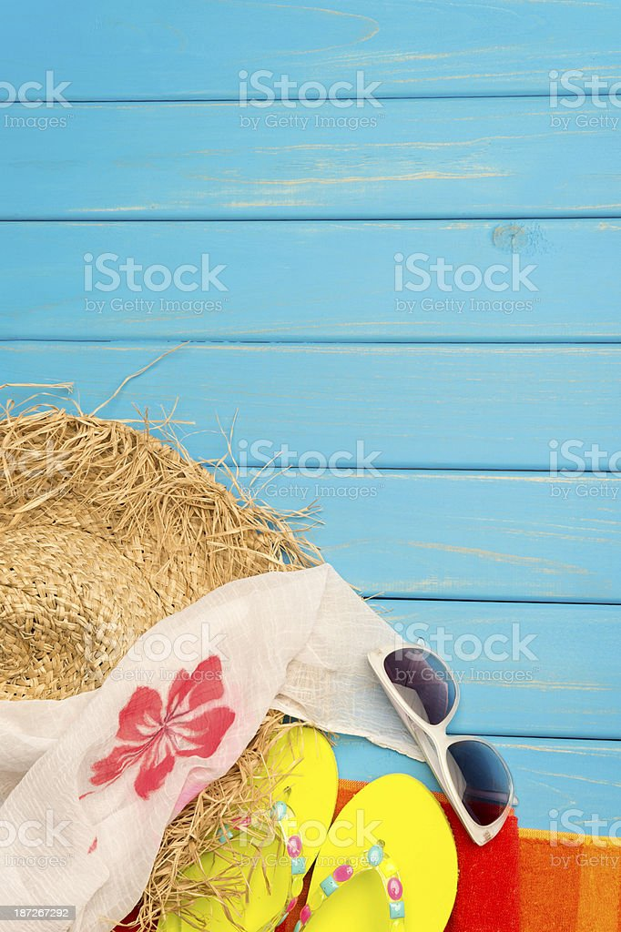 Beach scene with hat, thongs and blue wood decking royalty-free stock photo