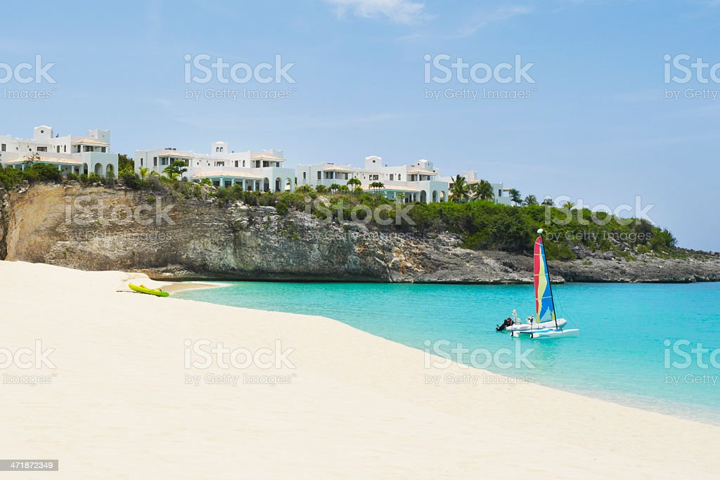 Beach scene with hotels and sail boat on water royalty-free stock photo