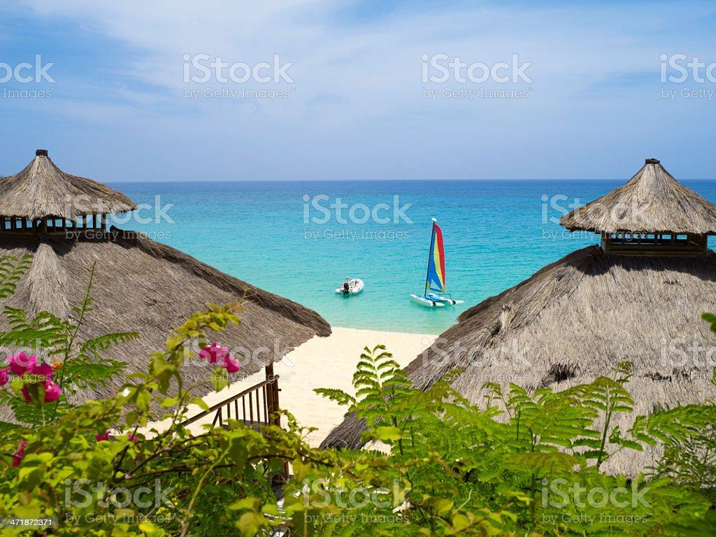 Beach scene with huts and sail boats stock photo