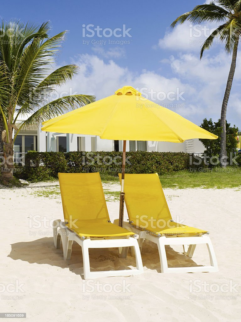 Beach scene with yellow lounge chairs and umbrella royalty-free stock photo