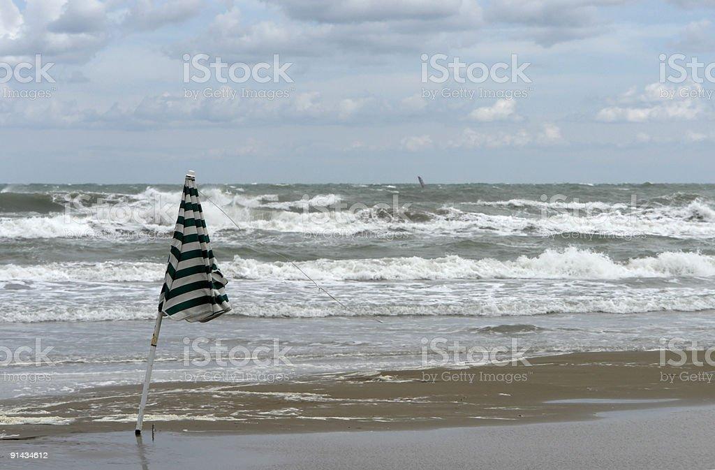 beach scenery with sunshade and wavy sea stock photo