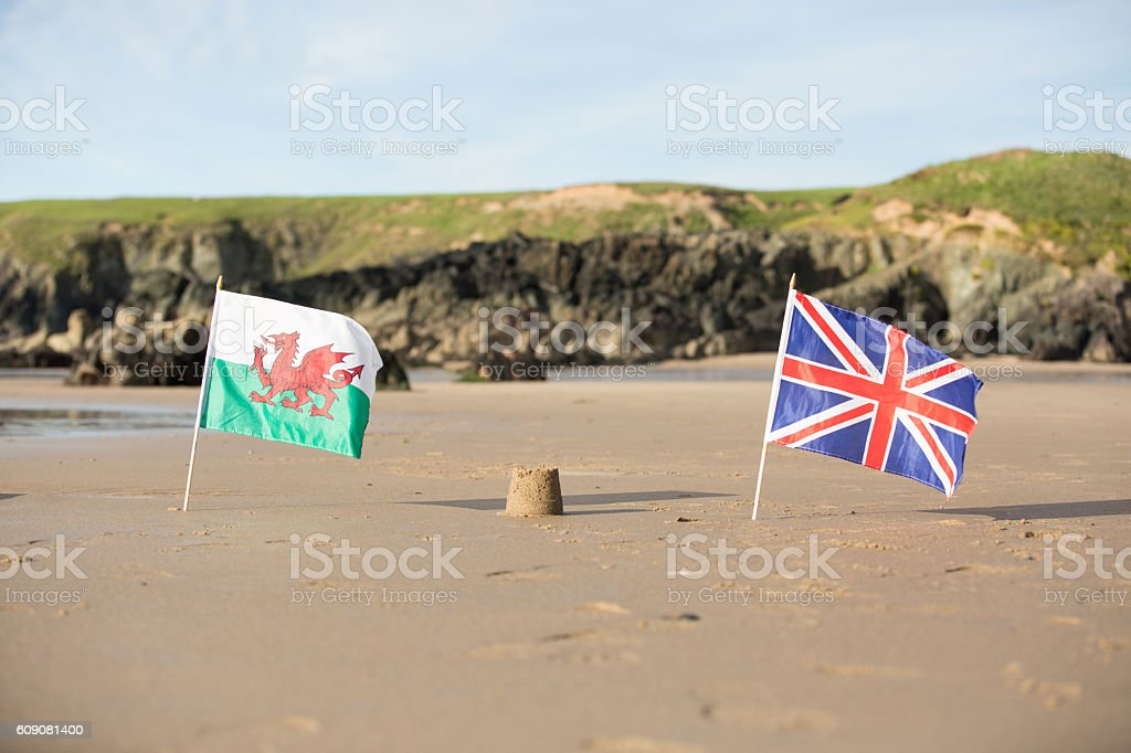 Beach, sea, sandcastle and  Welsh Flag and Union Jack stock photo