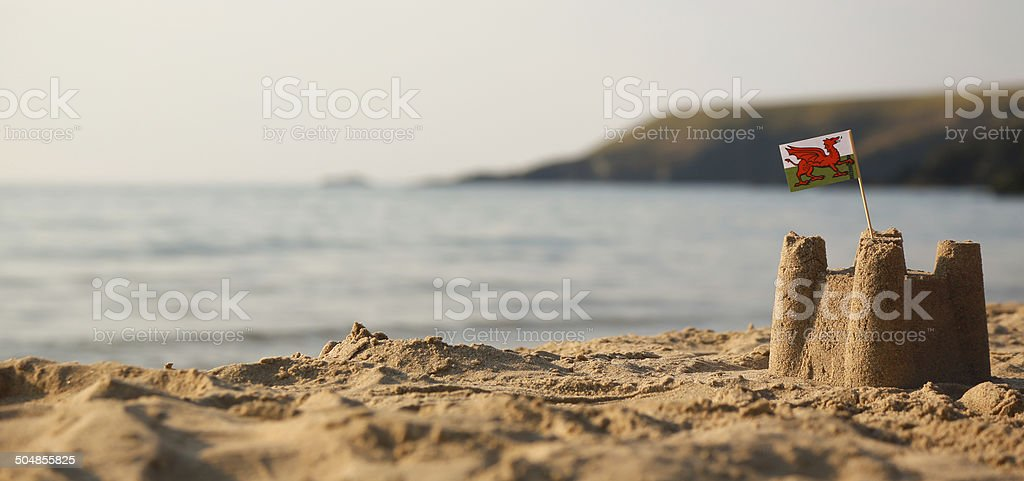 Beach, sea, sandcastle and  Welsh Flag stock photo