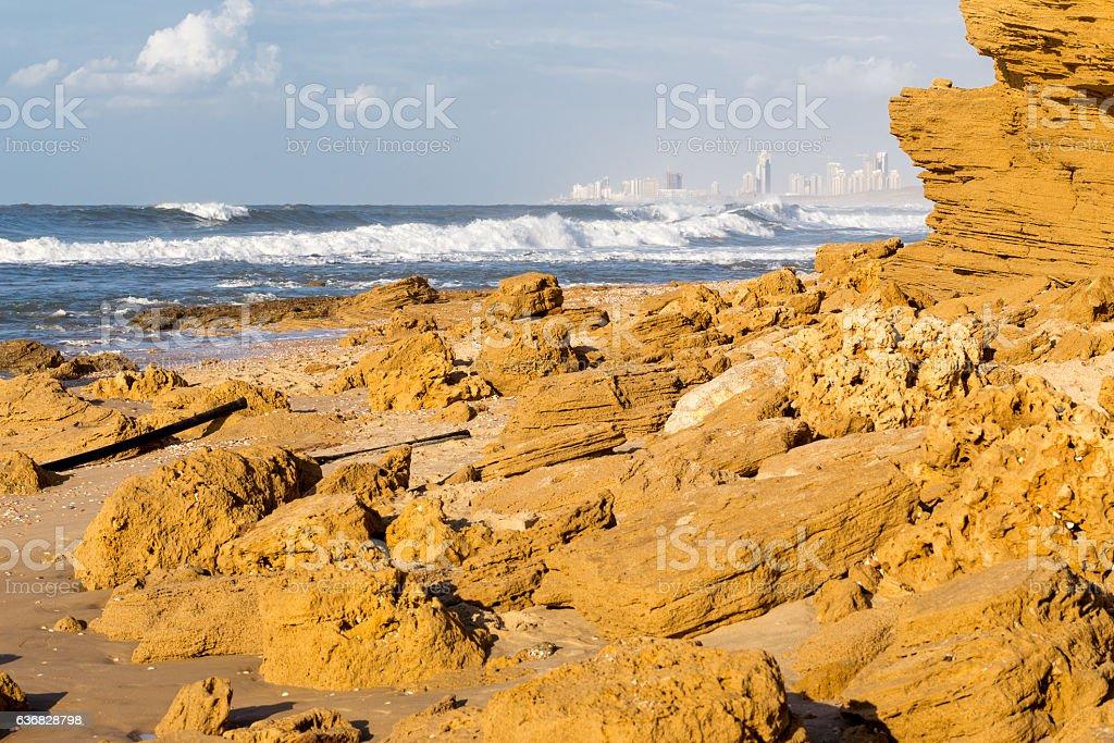 Beach sea wave splash city buildings cliff shore. stock photo
